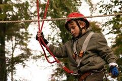 Ragazzo felice che scala nel parco di avventura Fotografia Stock Libera da Diritti
