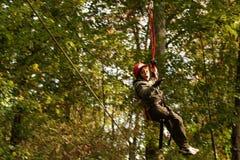 Ragazzo felice che scala nel parco di avventura Fotografie Stock
