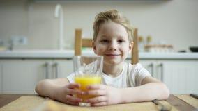 Ragazzo felice che si siede durante il pranzo con vetro di succo d'arancia e degli ossequi aspettanti con la macchina fotografica archivi video