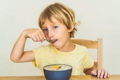 Ragazzo felice che si siede e che mangia una ciotola fresca del frullato con il mango, la frutta del drago, il granola ed i semi  immagine stock