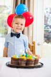 Ragazzo felice che si siede in Front Of Birthday Cake Immagini Stock