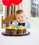 Ragazzo felice che si siede in Front Of Birthday Cake Fotografia Stock