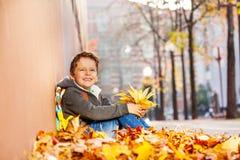Ragazzo felice che si siede nel mucchio della foglia con lo Zaino Fotografie Stock