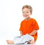 Ragazzo felice che si siede sul pavimento immagine stock