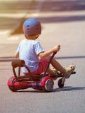 Ragazzo felice che sta sul hoverboard o sul gyroscooter con accesso del kart Immagini Stock Libere da Diritti