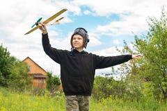 Ragazzo felice con l'aereo all'aperto fotografia stock