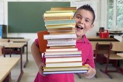 Ragazzo felice con la pila di libri in un'aula Fotografia Stock Libera da Diritti