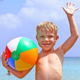 Ragazzo felice con la sfera di spiaggia Immagine Stock