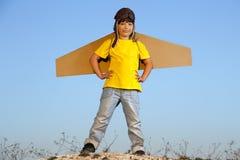 Ragazzo felice con le scatole di cartone delle ali contro il sogno del cielo della mosca Fotografie Stock