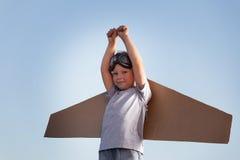 Ragazzo felice con le scatole di cartone delle ali contro il sogno del cielo della mosca Immagini Stock Libere da Diritti