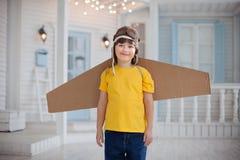 Ragazzo felice con le scatole di cartone delle ali nel sogno domestico del volo Fotografia Stock