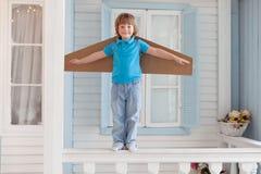 Ragazzo felice con le scatole di cartone delle ali nella casa Fotografia Stock Libera da Diritti