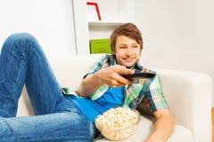 Ragazzo felice con popcorn che si rilassa sul sofà bianco Fotografie Stock