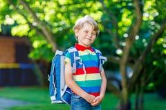 Ragazzo felice del bambino in camicia variopinta e zaino o cartella il suo primo giorno alla scuola o alla scuola materna Aria ap fotografie stock libere da diritti