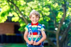 Ragazzo felice del bambino in camicia variopinta e zaino o cartella il suo primo giorno alla scuola o alla scuola materna Aria ap immagini stock