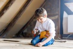 Ragazzo felice del bambino che aiuta con gli strumenti del giocattolo sul cantiere Un bambino divertente di 7 anni divertendosi s immagini stock