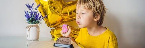 Ragazzo felice del bambino che celebra il suo compleanno e che soffia le candele sul dolce al forno casalingo, dell'interno Festa immagini stock libere da diritti