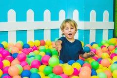 Ragazzo felice del bambino che gioca all'alta vista del campo da giuoco di plastica variopinto delle palle Bambino divertente div immagine stock libera da diritti
