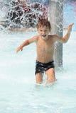 Ragazzo felice del bambino che ha divertimento in acqua fotografie stock libere da diritti