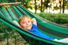Ragazzo felice del bambino che si trova in un'amaca in giardino Concetto di vacanze estive Il bambino sta riposando in natura Bam immagine stock libera da diritti