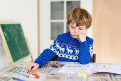 Ragazzo felice del bambino della scuola a casa che fa compito Fotografie Stock Libere da Diritti