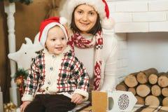 Ragazzo felice del bambino e della madre in cappelli dell'assistente di Santa con il contenitore di regalo Fotografia Stock Libera da Diritti