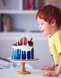 Ragazzo felice della testarossa sveglia, candele di salto del bambino sulla torta di compleanno al suo terzo compleanno immagini stock