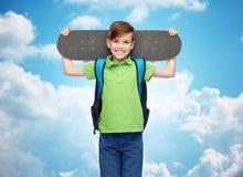 Ragazzo felice dello studente con lo zaino ed il pattino Fotografie Stock Libere da Diritti