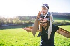 Ragazzo felice e padre del bambino che giocano con le ali fuori nella natura di primavera Fotografie Stock