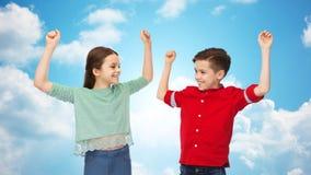 Ragazzo felice e ragazza che celebrano vittoria sopra il cielo Immagini Stock