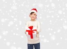 Ragazzo felice sorridente in cappello di Santa con il contenitore di regalo Immagine Stock