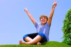 Ragazzo felice sull'erba con il calcolatore del ridurre in pani Immagini Stock