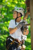Ragazzo felice, sveglio, giovane in maglietta bianca e casco divertendosi e giocando al parco di avventura, tenendo le corde e sc immagine stock