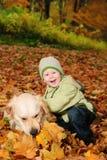 Ragazzo in fogli di autunno fotografie stock