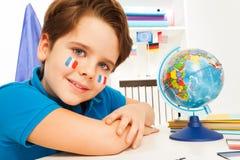 Ragazzo francese che impara geografia con il globo Fotografia Stock