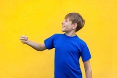 Ragazzo freckled divertente che tiene oggetto immaginario fotografie stock