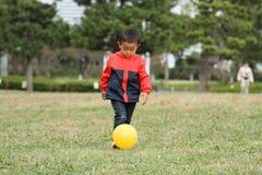 Ragazzo giapponese che dà dei calci ad una palla gialla sull'erba Fotografia Stock