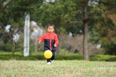 Ragazzo giapponese che dà dei calci ad una palla gialla sull'erba Immagini Stock