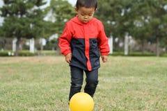 Ragazzo giapponese che dà dei calci ad una palla gialla sull'erba Immagine Stock