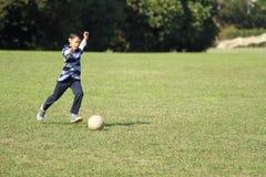 Ragazzo giapponese che gioca con il pallone da calcio Fotografia Stock