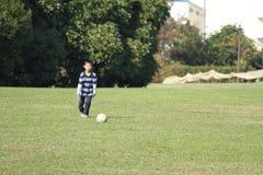 Ragazzo giapponese che gioca con il pallone da calcio Fotografie Stock