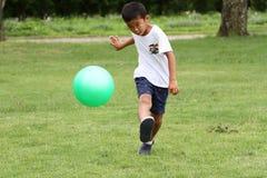 Ragazzo giapponese che gioca con il pallone da calcio Immagini Stock