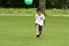 Ragazzo giapponese che gioca con il pallone da calcio Fotografia Stock Libera da Diritti