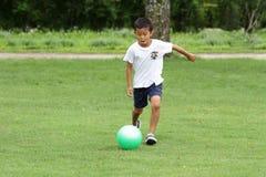 Ragazzo giapponese che gioca con il pallone da calcio Immagine Stock
