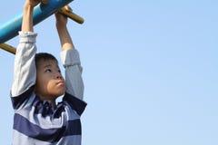 Ragazzo giapponese che gioca con le barre di scimmia Immagine Stock