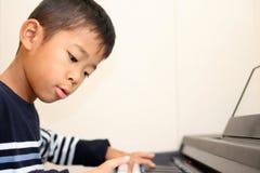 Ragazzo giapponese che gioca un piano Fotografia Stock Libera da Diritti