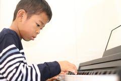 Ragazzo giapponese che gioca un piano Fotografia Stock