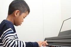 Ragazzo giapponese che gioca un piano Fotografie Stock Libere da Diritti