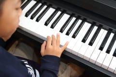 Ragazzo giapponese che gioca un piano Fotografie Stock