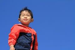 Ragazzo giapponese sotto il cielo blu Fotografia Stock